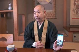 ツイート・ツールのスマホを手にする高野山・青巖寺の高井知弘副住職