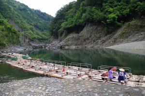 筏師・山本さんにインタビューする中川アナを遠景で