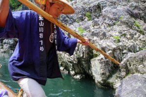 岩に櫂を差し込んで筏を進める筏師