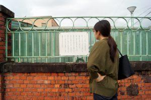 寺内町の赤レンガ塀を眺める中川アナ