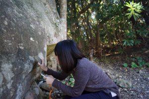 鳴子岩をたたいてみる中川アナ