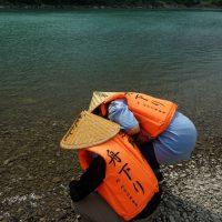 骨島で熊野川の水に触れる